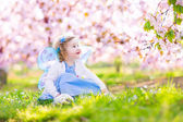 Curly toddler girl in fairy costume playing in fruit garden — Stock Photo