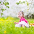 Cute toddler girl eating apple in a blooming garden — Stock Photo #46989639