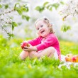 Cute toddler girl eating apple in a blooming garden — Stock Photo #46989661