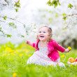 Cute toddler girl eating apple in a blooming garden — Stock Photo #46990009