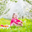Cute toddler girl eating apple in a blooming garden — Stock Photo #46990035