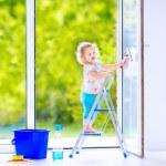 Little girl washing a window — Stock Photo #46990599