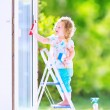 Little girl washing a window — Stock Photo #46990911
