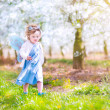 Cute toddler girl eating apple in a blooming garden — Stock Photo #46990951