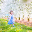 Cute toddlger girl in fairy costume playing in a blooming garden — Stock Photo #46990959