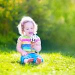Happy toddler girl eating ice cream in a garden — Stock Photo #46991069
