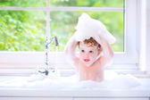 Funny baby girl playing with water and foam in a big kitchen sin — Stock Photo