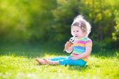 Happy toddler girl eating ice cream in a garden — Stock Photo