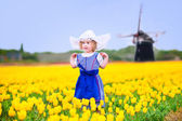 Little girl in a national Dutch costume in tulips field with windmill — Stock Photo