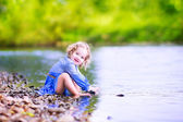 Little girl playing at river shore — Stock Photo