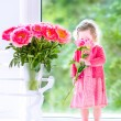Toddler girl playing with peony flowers — Stock Photo #47035133