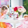 Toddler girl playing tea party with a doll — Stock Photo #47035615