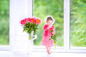 Toddler girl playing with peony flowers — Stock Photo