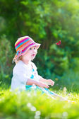 Toddler girl playing with butterfly — Stock Photo