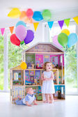 Baby brother and sister playing with a doll house — Stock Photo
