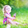 Funny girl eating ice cream in the garden — Stock Photo #48041529