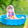 Toddler girl playing wil balls in the garden — Stock Photo