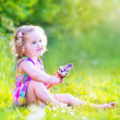 Funny girl eating ice cream in the garden — Stock Photo #48041565