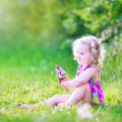 Funny girl eating ice cream in the garden — Stock Photo #48041955