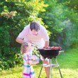 Father and daughter grilling in the garden — Stock Photo #48041987
