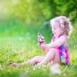 Funny girl eating ice cream in the garden — Stock Photo #48042097