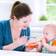 Baby boy eating his first solid food — Stock Photo #48042147