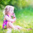 Funny girl eating ice cream in the garden — Stock Photo #48042597