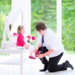 Father helping his daughter to put on a shoe — Foto Stock