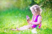 Funny girl eating ice cream in the garden — Stock Photo