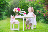 Toddler girl playing tea party with a doll — Stock Photo