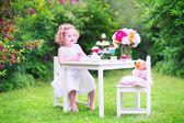 Kleinkind mädchen spielen teeparty mit einer puppe — Stockfoto