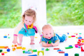 Brother and sister playing with colorful blocks — 图库照片