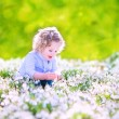 Happy girl playing with first spring flowers — Stock Photo