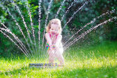 Little girl playing with garden sprinkler — Stock fotografie