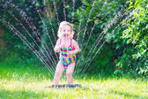 Little girl playing with garden sprinkler — Stock Photo