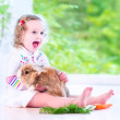 Little girl playing with a bunny — Stock Photo #49279105