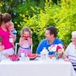 Family eating fruit in the garden — Stock Photo #49279185