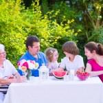 Family eating fruit in the garden — Stock Photo #49279223