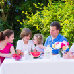 Family eating fruit in the garden — Stock Photo #49279359