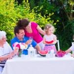 Family eating fruit in the garden — Stock Photo #49279453