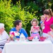 Family eating fruit in the garden — Stock Photo #49279507