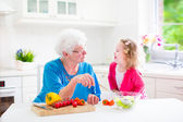 Grandmother and little girl making salad — Stock fotografie