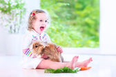 Little girl playing with a bunny — Photo