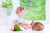 Little girl playing with a bunny — Stock fotografie