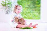 Little girl playing with a bunny — Stockfoto