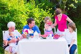Family eating fruit in the garden — Stock Photo