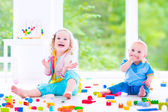 Brother and sister playing with colorful blocks — Stock Photo