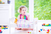 Little girl playing with a teddy bear — Stockfoto