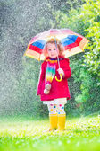 Little girl playing in the rain — Stock Photo