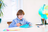 Smiling boy doing homework — Stock Photo